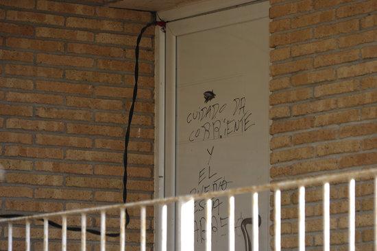 Pla tancat de la porta duna casa de la urbanitzacio dAigues bones de Caldes de Malavella amb el cable de la llum punxada i unes lletres a la porta avisant que enrampa el 27 de gener de 2020 Horitzontal