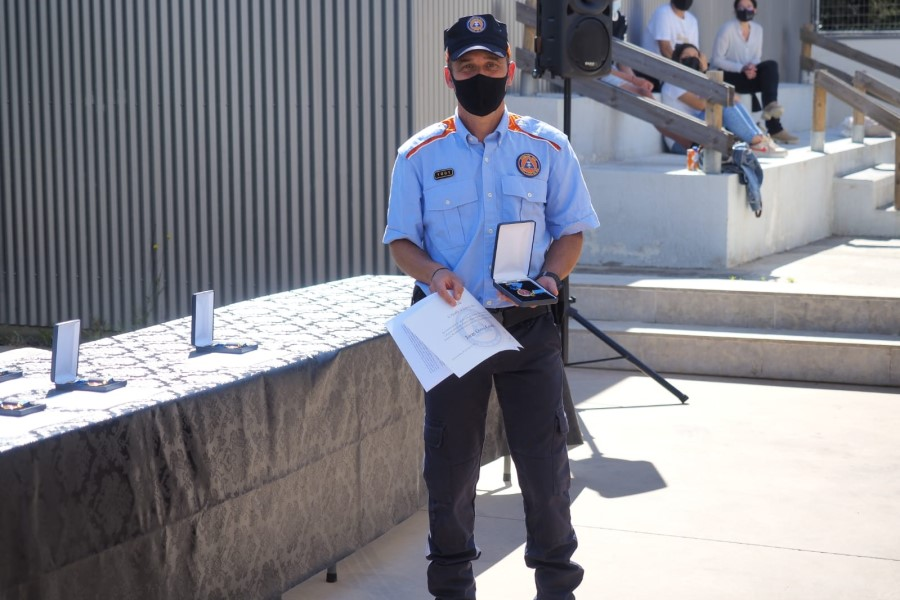 Un dels voluntaris de Protecció Civil mostrant la medalla blava