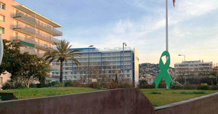 La façana de l'Ajuntament i el llaç de la rotonda, de color verd pel Dia Mundial Contra el Càncer