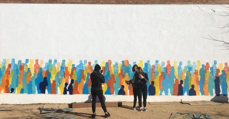 Els alumnes del Batxillerat Artístic del Coll i Rodés pinten el pati infantil de l'escola Pere Torrent
